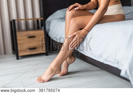 Awakened Woman Sitting On The Edge Of The Bed Bare Feet On The Floor. Side View Of Beautiful Female