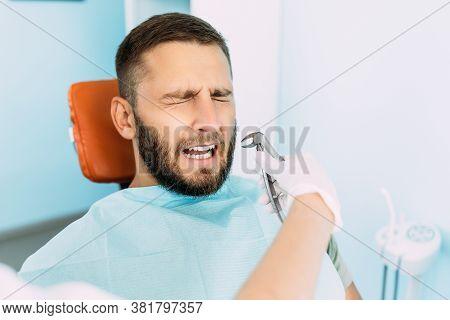 A Man Treats His Teeth At The Dentist. Dental Examination At The Dentist. Dental Care. A Man Is Afra