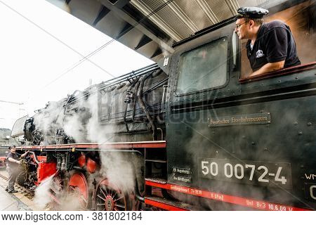 Goeppingen, Germany - September 19, 2015: A Train Driver Is Starting The Engines Of An Old Steam Loc