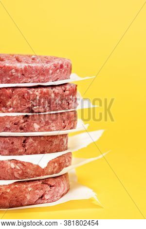 Close-up With A Stack Of Burger Patties Against A Yellow-colored Background. Raw Beef Burger Patties