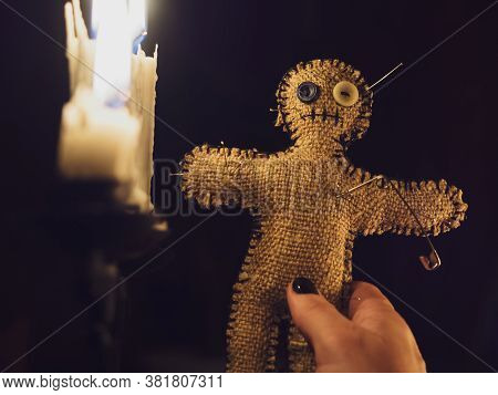 A Girl Sticks Pins In A Voodoo Doll Made Of Burlap, Close-up. The Voodoo Doll In A Mysterious Candle