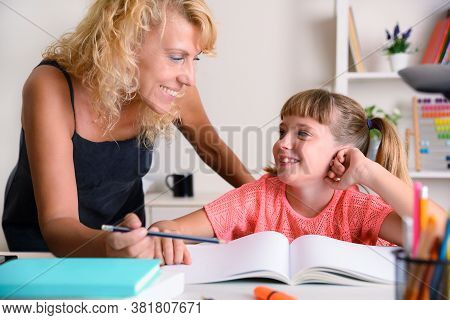 Mother And Daughter Looking At Each Other With Complicity At The Time Of School Studies In The Study