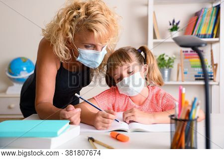 Mother Explaining Lesson To Daughter Studying Confined By Coronavirus In The Study Room At Home