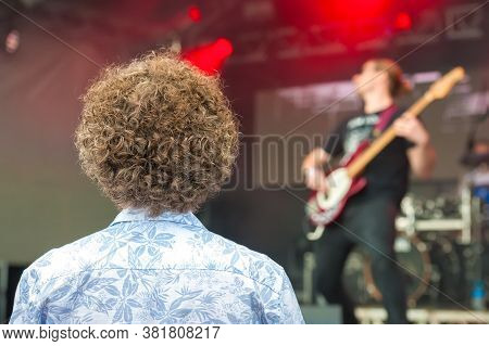 Young Person With Very Curly Hair Watching A Rock Band On Stage