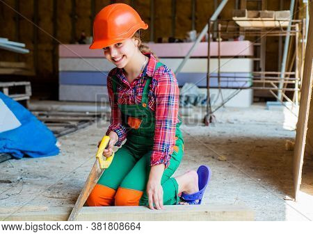 Little Girl Working With Wood. Kid Sawing A Plank In Carpentry. Working With Wood In A Garage. Happy