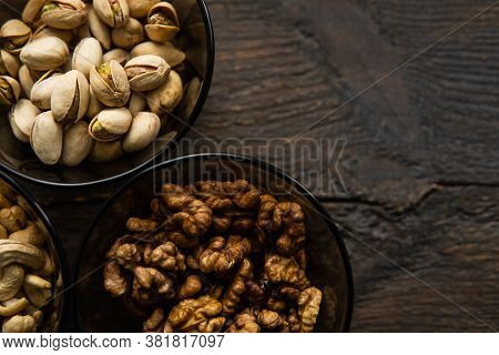 Walnut, Pistachio And Cashew In A Small Plates Which Standing On A Black Table. Nuts Is A Healthy Ve