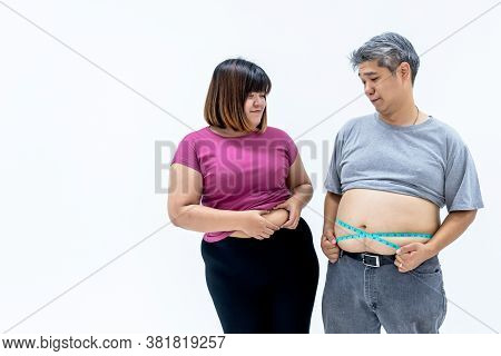 Portrait Images Of Asian Couple, Fat Man And Woman, Are Looking At Each Other's Belly Fat, On White