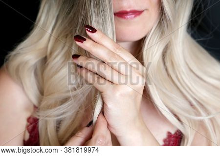 Blonde Woman With Red Manicure Straightens Her Long Curly Hair. Female Beauty, Make Up, Lady With Lu