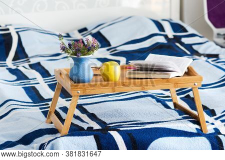 Breakfast Tray On The Bed With A Book And Flowers. Cozy Home Interior. Blue Bedspread On The Bed. Th