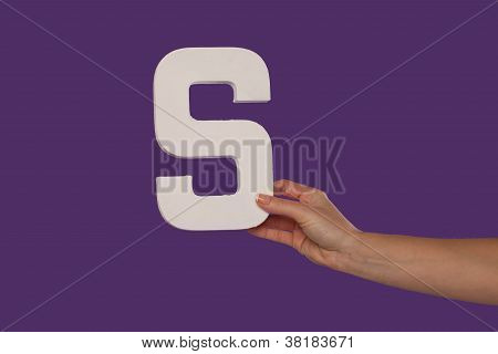Female Hand Holding Up The Letter S From The Right