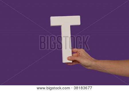 Female Hand Holding Up The Letter T From The Right