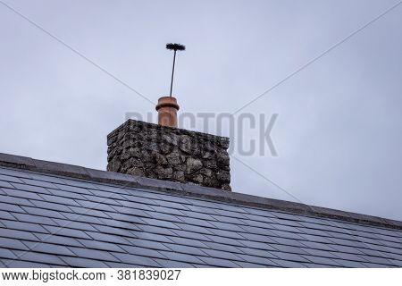 Chimney Cleaning Brush Sticking Up Out Of A Chimney Pot