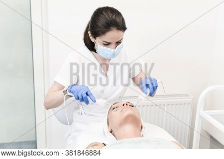 The Young Female Client Of Cosmetic Salon Having Microcurrent Procedure On Her Face With Special Dev
