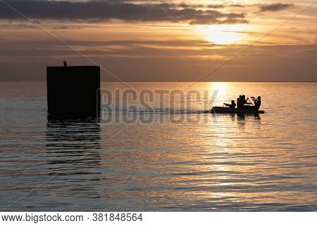 Urk, The Netherlands- December 28, 2009: Artist In Rowing-boat Pulls A Floating House He Has Build F