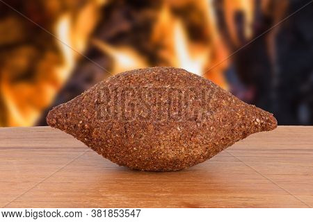 Kibe. Traditional Brazilian Snack Food. Isolated On Defocused Fire In The Background. Copy Space