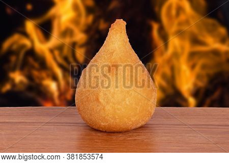 Coxinha. Traditional Fried Brazilian Food With Chicken. Background With Defocused Fire. Space Copy