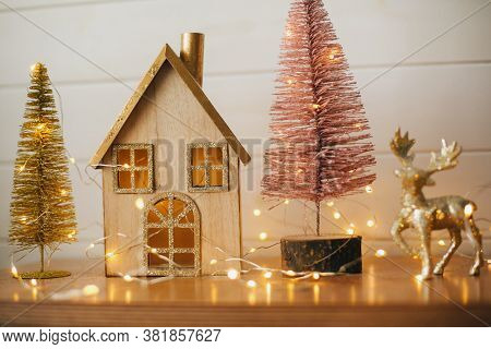 Stylish Christmas Wooden House, Glitter Christmas Tree And Golden Reindeer In Festive Lights. Modern