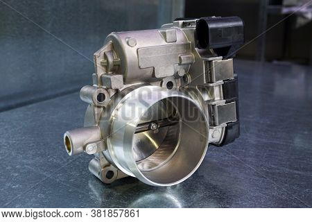 New Throttle Valve Of A Modern Car Engine On A Steel Background. Car Service And Spare Parts.