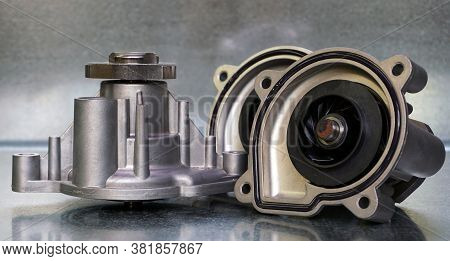 Coolant Pump Of A Modern Car On A Steel Background. Shown From The Outside And From The Impeller Sid