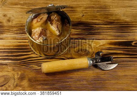 Open Tin Can Of Sardine Fish And Can Opener On Wooden Table