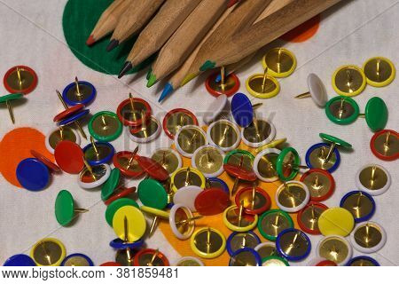 Thumbtacks And Colored Pencils Scattered On A Colored Plane, Horizontal Image