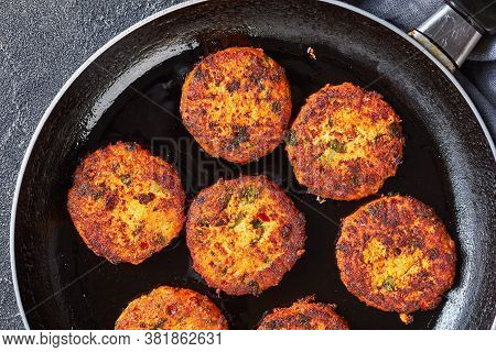 Fried Thai Fish Cakes In A Skillet On A Concrete Table, Horizontal View From Above, Close-up, Flat L