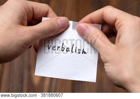 Concept Of Cancelling. Hands Closeup Tearing A Sheet Of Paper With Inscription Verbalism