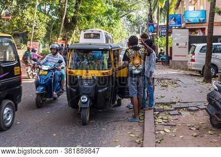 Candolim, North Goa, India - November 23, 2019: Tourists Agree With Driver Of Auto Rickshaw Or Tuk-t