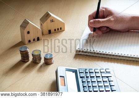 Selective Focus At Men Hand Take Note On Paper Notebook. With Blurred Calculator And House Mock Up O