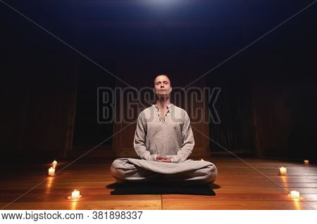 A Portrait Of An Attractive Caucasian Man Sits In Cotton Robes In A Lotus Pose In A Dark Wooden Prac