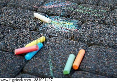 Colored Chalk On Playground With Drawings On Street.children Drawing On The Street. Drawing Lessons