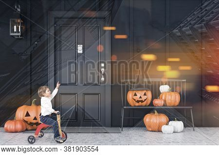 Little Boy On Tricycle Riding Near Black Bench With Carved Pumpkins In Front Of Modern House With Bl