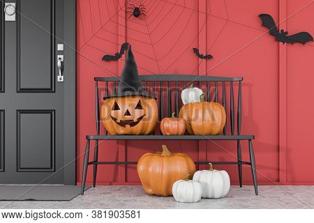Carved Pumpkins, Bats And Spiders On Black Bench Near Black Front Door Of Modern House With Red Wall