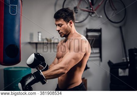 A Young Athlete With A Muscular Torso Is Warming Up With A Punching Bag In His Garage.