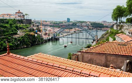Panoramic View On River Douro With Riverboats Sailing, Double-deck Metal Arch Bridge And City Porto.