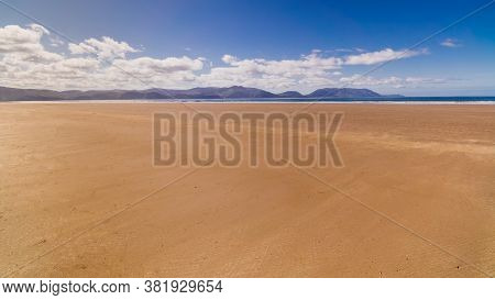Long, Beautiful Sandy Inch Beach With Mountains In Background. Summer Day With Blue Sky On Empty Bea