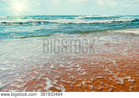 Sea Surf To The Beach Shore Sunny Day Summer. Sea Water Runs Onto The Sandy Shore. Blue Waves On A S