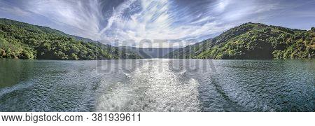 Panorama Of Boat Wake With A River Landscape With Mountains In The Background And A Sky With Sun And