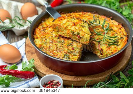 Vegetable Kugel Of Zucchini, Carrots, Potatoes, Garlic And Turmeric In A Round Baking Dish. Dish Of