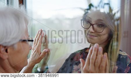 Young Lady In Quarantine Speaking With Her Grandmother Through The Glass Window. Protecting Vulnerab