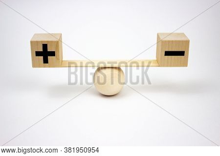 Plus And Minus Or Positive And Negative Symbols On Wooden Blocks Are In Balance On A Wooden Seesaw.