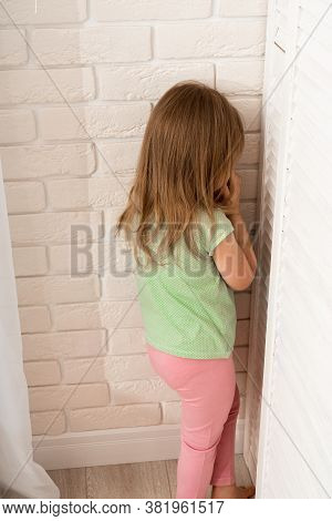 Little Blonde Girl Is Punished And Stands Alone In A Corner And Cries. The Child Misbehaved And Was