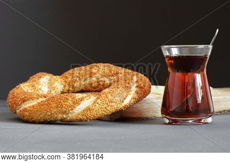 Crispy Turkish Traditional Bagel / Simit With Sesame And Glass Of Turkish Black Tea On Rustick Backg