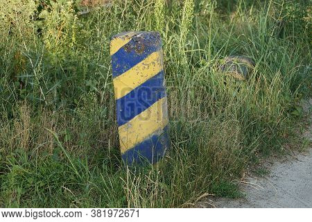 One Old Striped Concrete Post, The Limiter Stands In The Green Grass On The Street By The Road