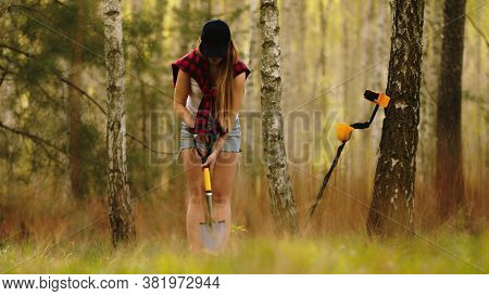 Search With A Metal Detector. Young Woman Digging Detected Metal In The Forest. High Quality Photo