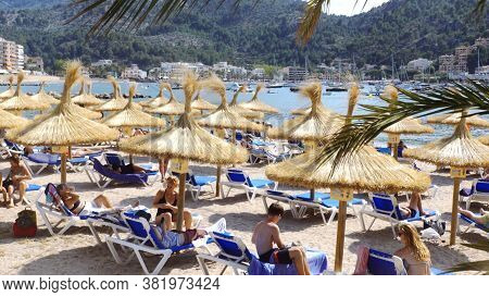 Port De Soller Spain - 06 10 2019 Straw Umbrellas And Bathers On The Beach. High Quality Photo