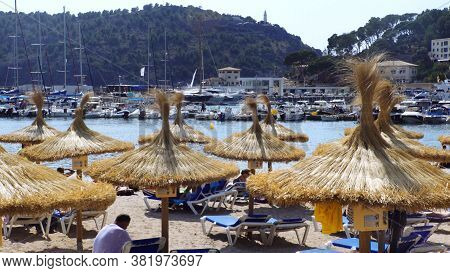 Port De Soller. Spain - 06 10 2019: Straw Umbrellas And Bathers On The Beach. High Quality Photo