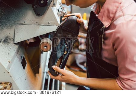 Woman cobbler working on machine in her shoemaker workshop adjusting the settings