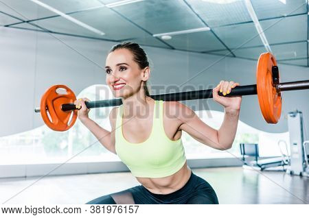 Full length low-angle view of a beautiful determined young woman holding a barbell behind the neck