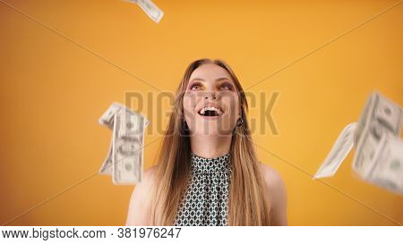 Young Fashionable Posh Woman Throwing Cash In The Air Isolated On The Orange Background. Slow Motion